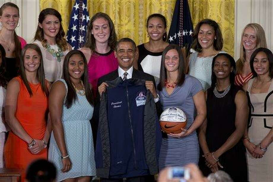 President Barack Obama poses with a jacket and an autographed ball during a ceremony in the East Room of the White House to honor the University of Connecticut Huskies for their 2013 NCAA Women's Basketball Championship win, Wednesday, July 31, 2013, in Washington. University of Connecticut Huskies seen from top left are, Heather Buck, Stefanie Dolson, Breanna Stewart, Kiah Stokes and assistant coaches Marisa Moseley and Shea Ralph, from bottom left, Caroline Doty, Kaleena Mosqueda-Lewis, Kelly Faris, Brianna Banks and Bria Hartley.  (AP Photo/Carolyn Kaster) Photo: AP / AP