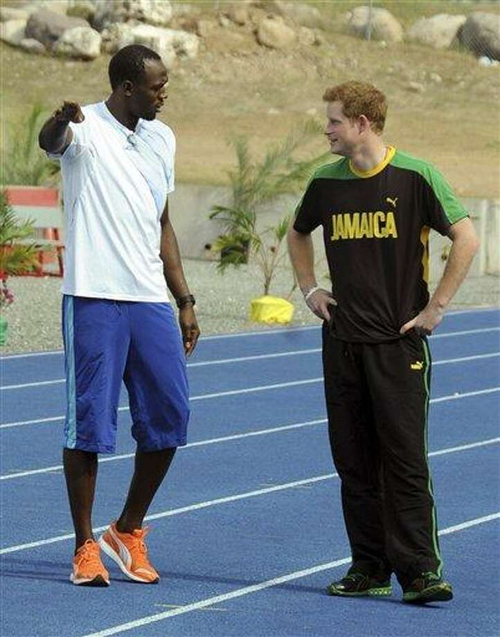 Britain's Prince Harry, right, listens to Olympic sprint champion Usain Bolt, before running against him in a mock race Tuesday in Kingston, Jamaica. The prince is in Jamaica as part of the Diamond Jubilee tour in honor of Queen Elizabeth II, who celebrates 60 years on the throne this year.  Associated Press Photo: AP / AP