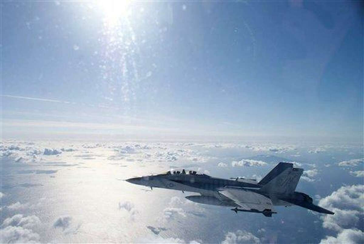 """In this Thursday, Dec. 20, 2012 photo provided by U.S. Navy, a F/A18F Super Hornet with the VFA-102, """"Diamondbacks"""" flies above cloud during the squadron's training mission in Japan. The squadron is assigned to the USS George Washington aircraft carrier. The United States has more than 50,000 troops in Japan and in a region anxious over the rise of China's military might, squadrons like the Diamondbacks are an important component of the U.S. military presence in the Pacific. (AP Photo/U.S. Navy, Douglas Spence)"""