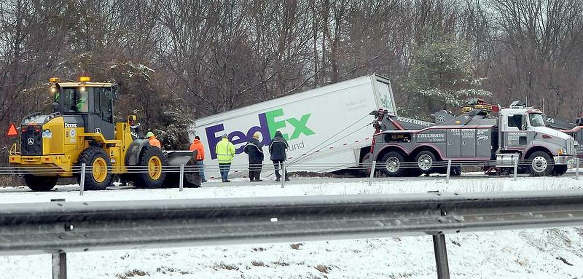 Emergency crews pull a tractor-Trailer from a ditch on the I-91 Exit 13 northbound ramp in Wallingford Tuesday morning March 19, 2013. Photo by Peter Hvizdak / New Haven Register