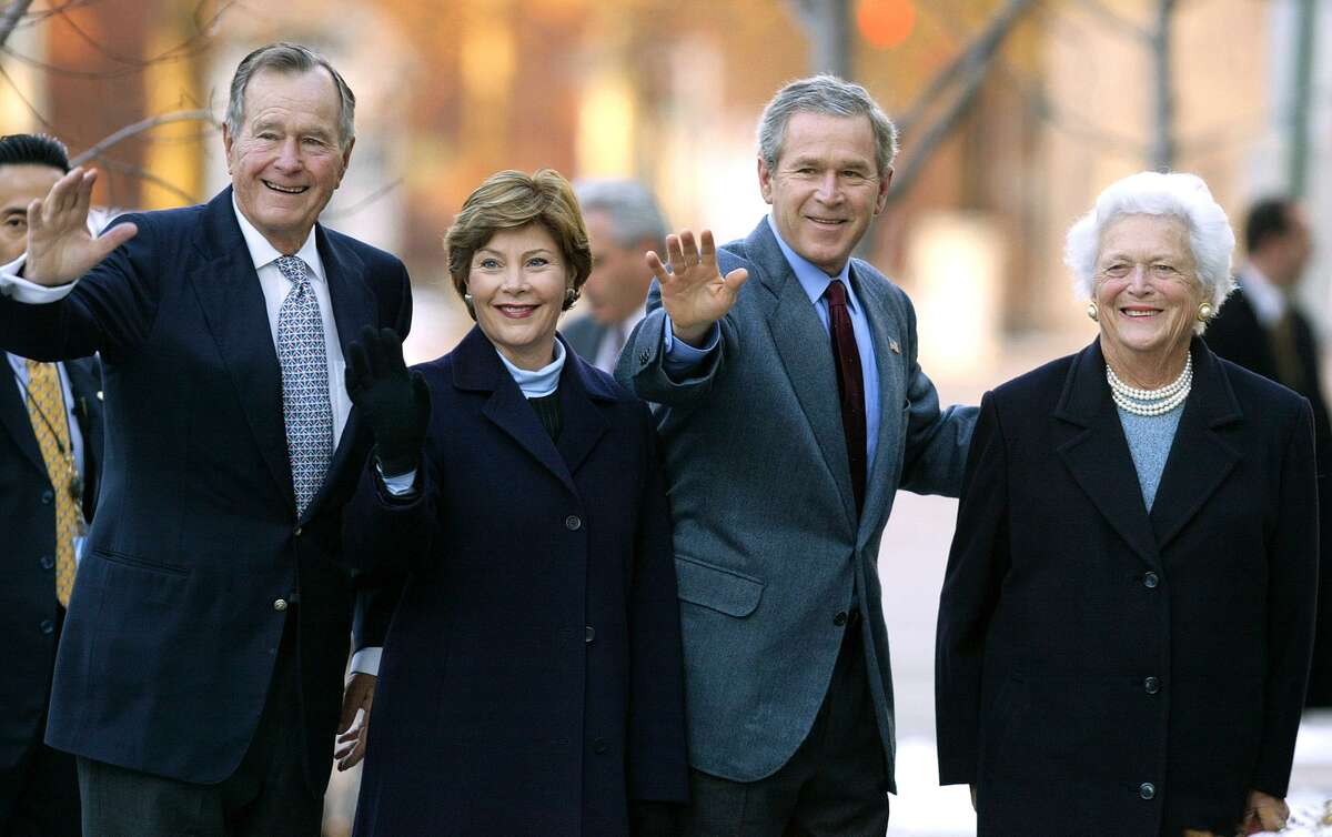 In this Dec. 7, 2003 file photo, former President George H.W. Bush, then first lady Laura Bush, then President George W. Bush, and former first lady Barbara Bush wave to reporters outside St. John's church in Washington. Laura Bush and Barbara Bush are headlining a Dallas conference on first ladies. Presidential historian Doris Kearns Goodwin will moderate a conversation with the former first ladies on Monday. (AP Photo/Evan Vucci, File)