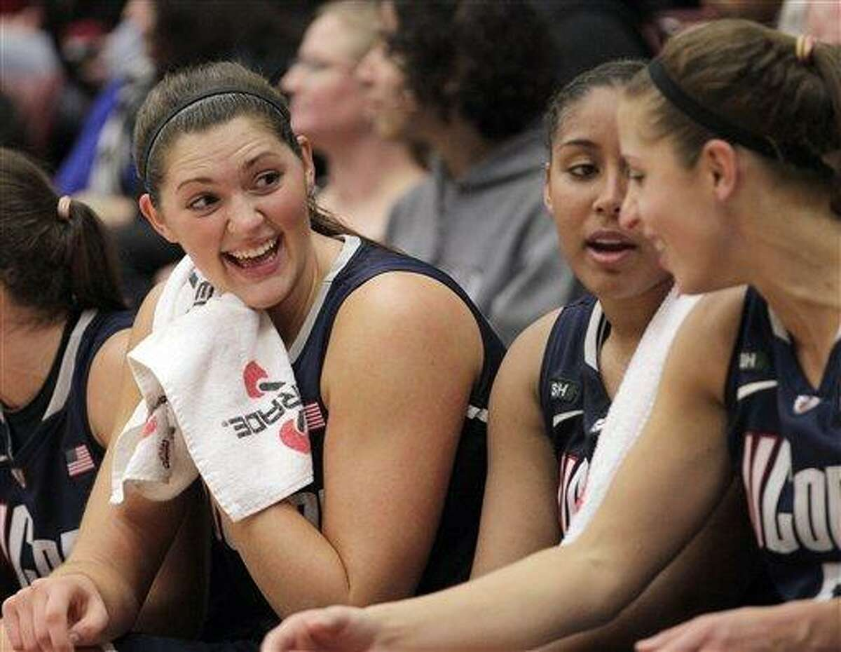 Connecticut center Stefanie Dolson, left, Kaleena Mosqueda-Lewis, center, and Caroline Doty, right, chat on the bench during the second half of their 61-45 victory against Stanford in an NCAA college basketball game in Stanford, Calif., Saturday, Dec. 29, 2012. (AP Photo/Tony Avelar)