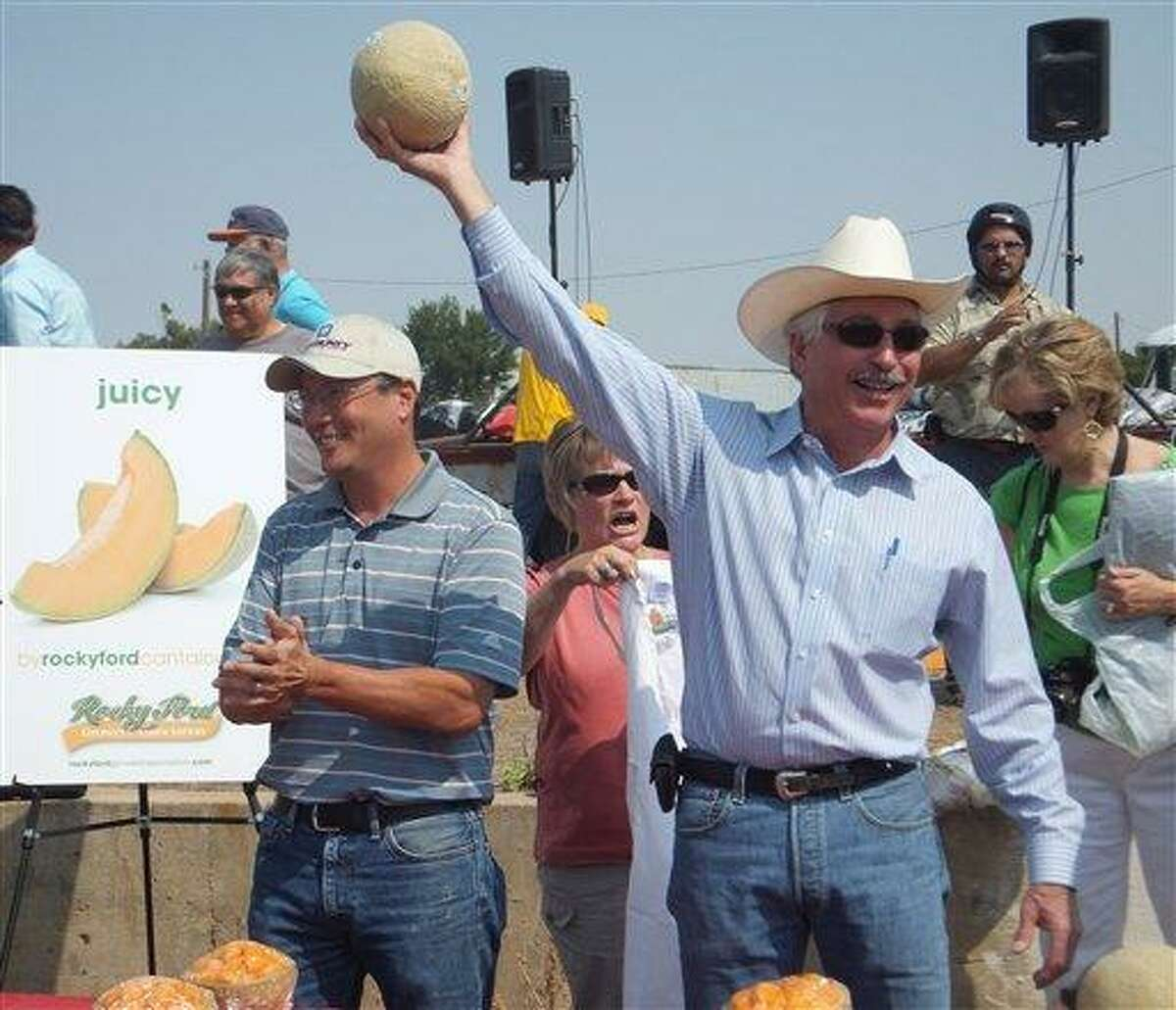 """Colorado Agriculture Secretary John Salazar, right, holds up a Rocky Ford cantaloupe and declares it """"the sweetest, best melon in the country"""" at the Arkansas Valley Fair in Rocky Ford, Colo., Saturday. A year after melons from southeast Colorado were the source of a nationwide listeria outbreak that killed 30 and sickened hundreds, growers in Rocky Ford have spent nearly $1 million in safety upgrades and say they're having a strong season with higher prices and strong demand. (AP Photo/Kristen Wyatt)"""