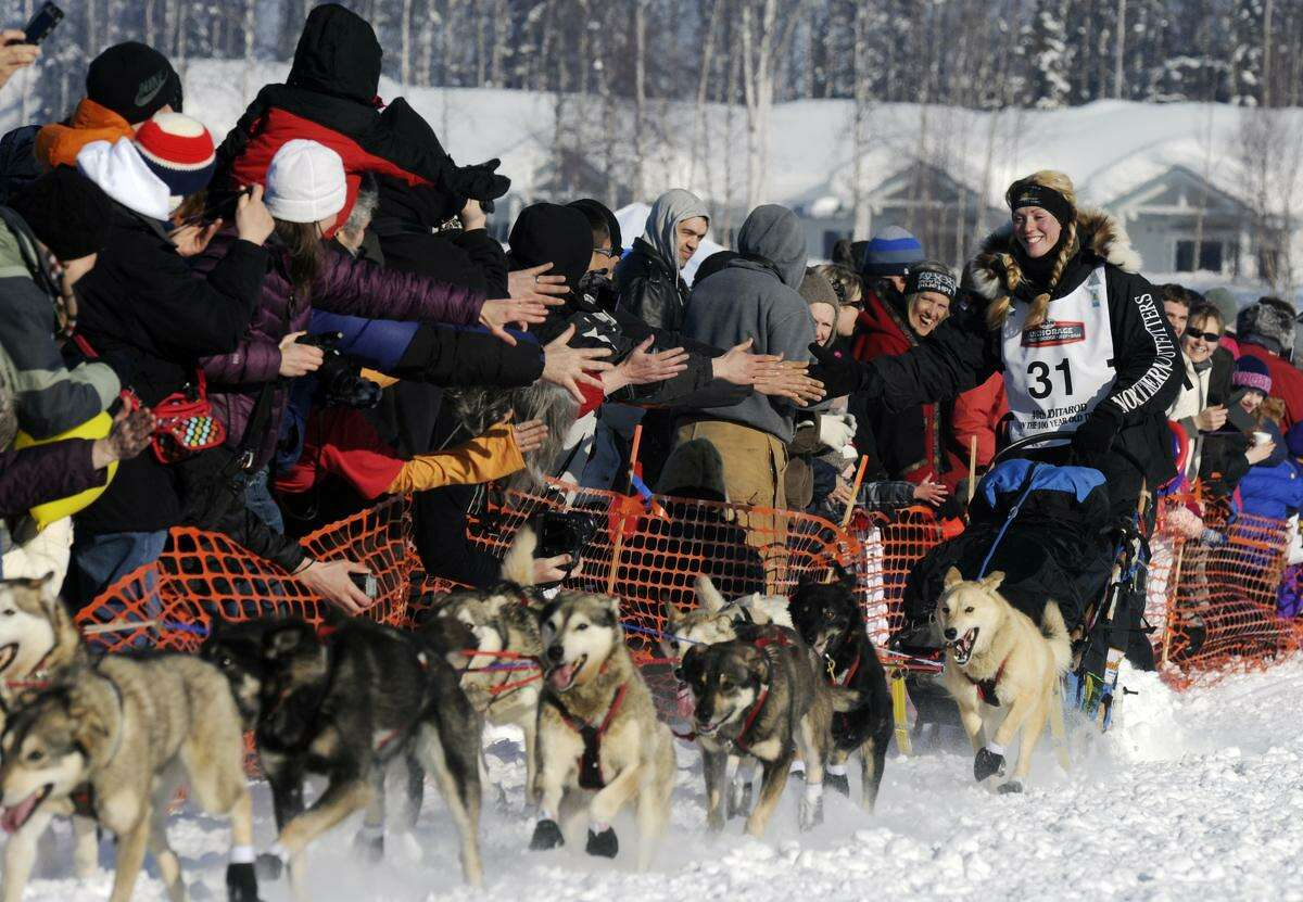 Kristy Berington greets fans as she makes her way through the trail during the official start of the Iditarod Trail Sled Dog Race, Sunday, in Willow, Alaska. Associated Press