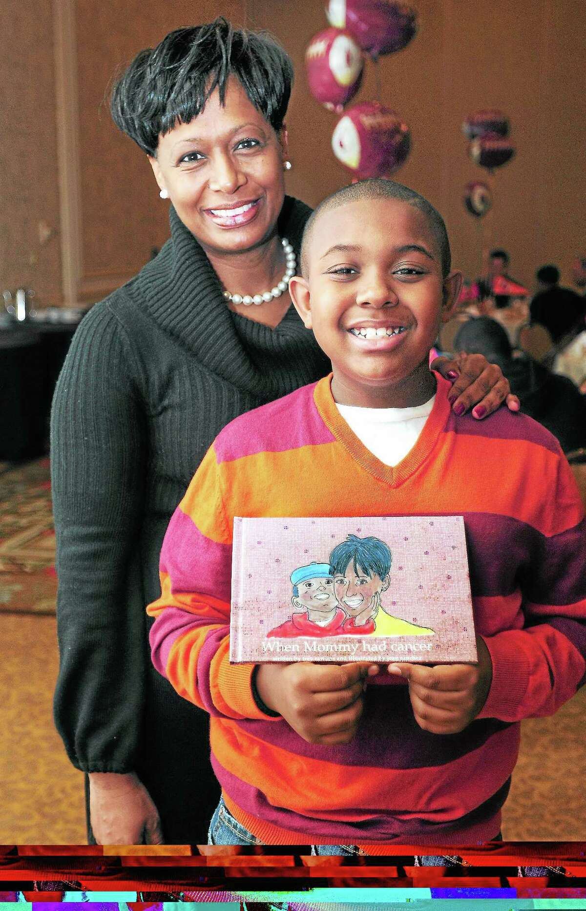 """Walter Camp Essay Contest winner James, """"Trey"""" Rawlins, III, is photographed with his mother, Veronica Marion, and the book he wrote, When Mommy had cancer, at the Walter Camp Alumni Brunch at the Omni New Haven Hotel at Yale on 1/11/2013.Photo by Arnold Gold/New Haven Register AG0480B"""