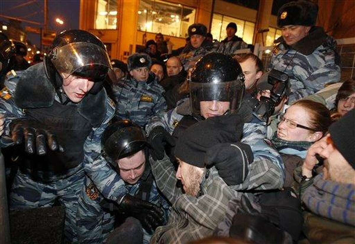 Russian police officers detain demonstrators attempting to hold an unsanctioned protest in Moscow Monday. Demonstrators contested the outcome of the Russian presidential election Monday, pointing to a campaign heavily slanted in Russian Prime Minister Vladimir Putin's favor and to reports of widespread violations in Sunday's ballot. Associated Press