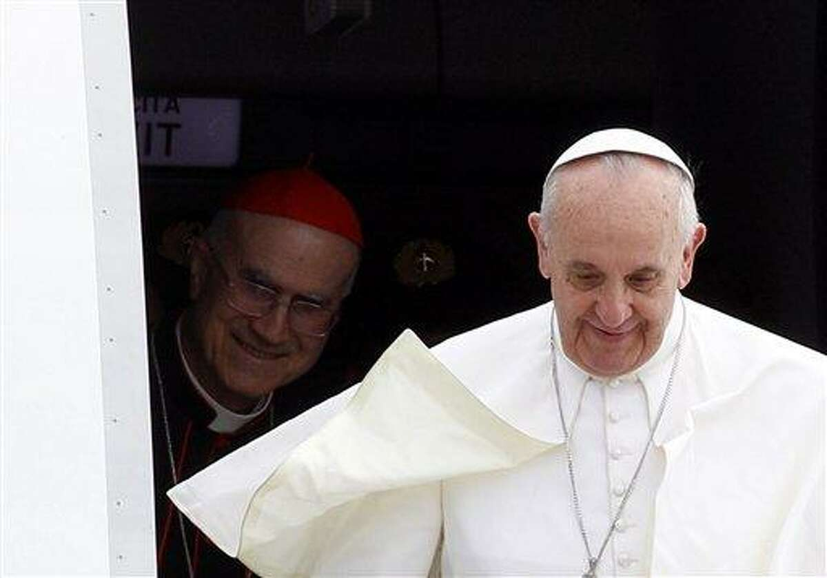 Pope Francis, followed by Vatican Secretary of State Cardinal Tarcisio Bertone, disembarks from the plane after landing from Rio de Janeiro, Brazil, at Ciampino's military airport, on the outskirts of Rome, Monday, July 29, 2013. The pontiff returned after a week in Brazil. (AP Photo/Riccardo De Luca)