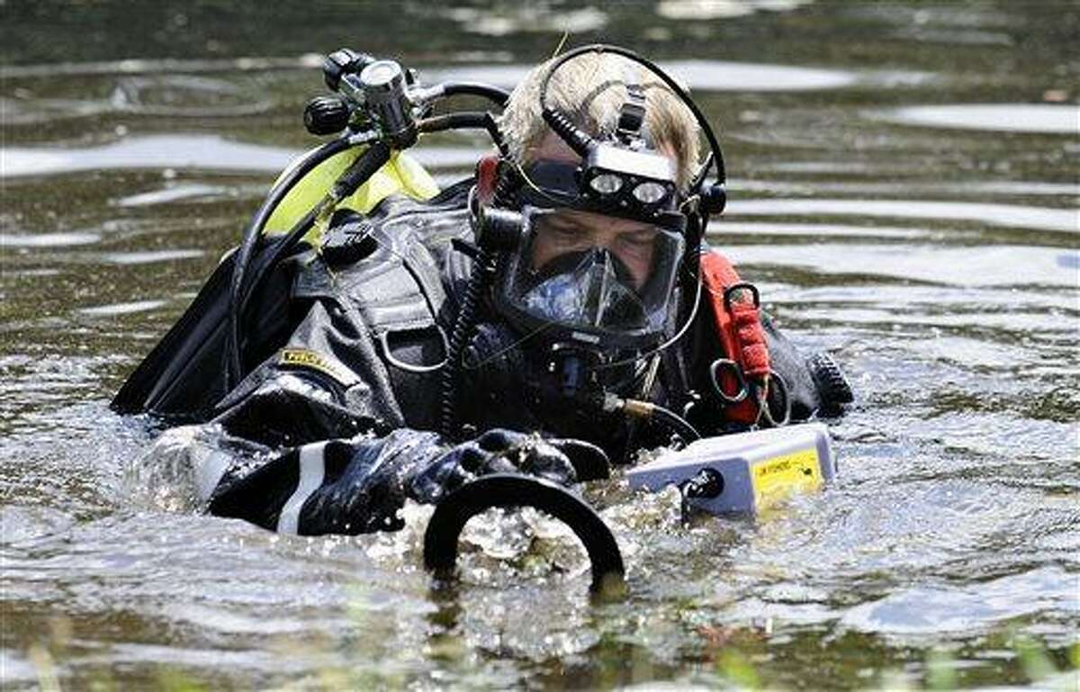 A Connecticut State Police dive team member searches Pine Lake in Bristol, Conn., the hometown of the former New England Patriots player Aaron Hernandez, Monday, July 29, 2013. Police divers were in Pine Lake on Monday and other officers could be seen combing the water's edge. Hernandez has pleaded not guilty to murder in the death of Odin Lloyd, a 27-year-old Boston semi-professional football player. (AP Photo/Jessica Hill)