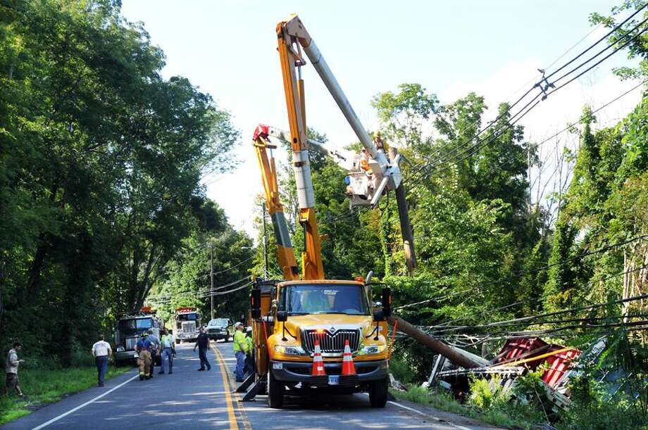 Employees from Connecticut Light & Power remove a telephone pole from wires following an accident where an 18-wheeler slid off the Route 68 into an embankment in Durham Monday afternoon. Catherine Avalone - The Middletown Press / TheMiddletownPress