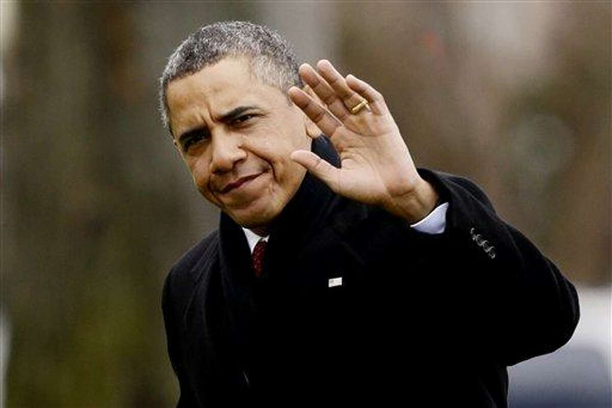 President Barack Obama waves to reporters as he steps off the Marine One helicopter and walks on the South Lawn Thursday at the White House in Washington, as he returns early from his Hawaii vacation for meetings on the fiscal cliff. Associated Press