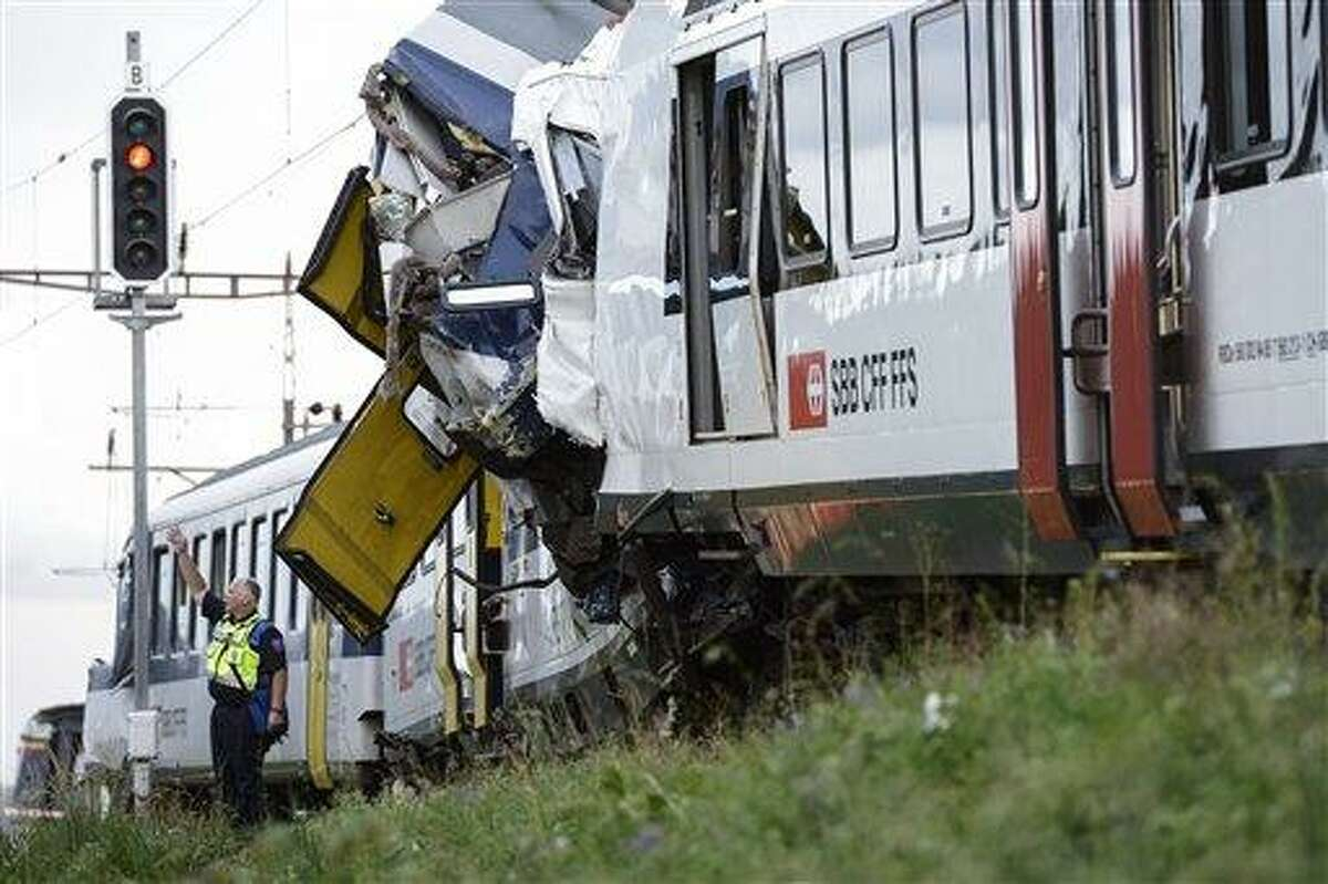 A policeman works at the site where two passenger trains collided head-on in Granges-pres-Marnand, western Switzerland, Monday, July 29, 2013. Police say at least 44 people were injured, four of them seriously. (AP Photo/Keystone, Laurent Gillieron)