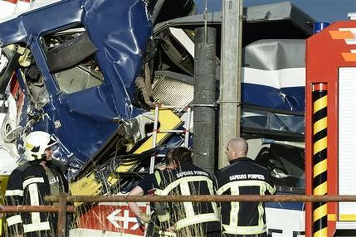 Rescue personnel work at the site where two passenger trains collided head-on in Granges-pres-Marnand, western Switzerland, Monday, July 29, 2013. Numerous people have been injured. (AP Photo/Keystone, Laurent Gillieron)
