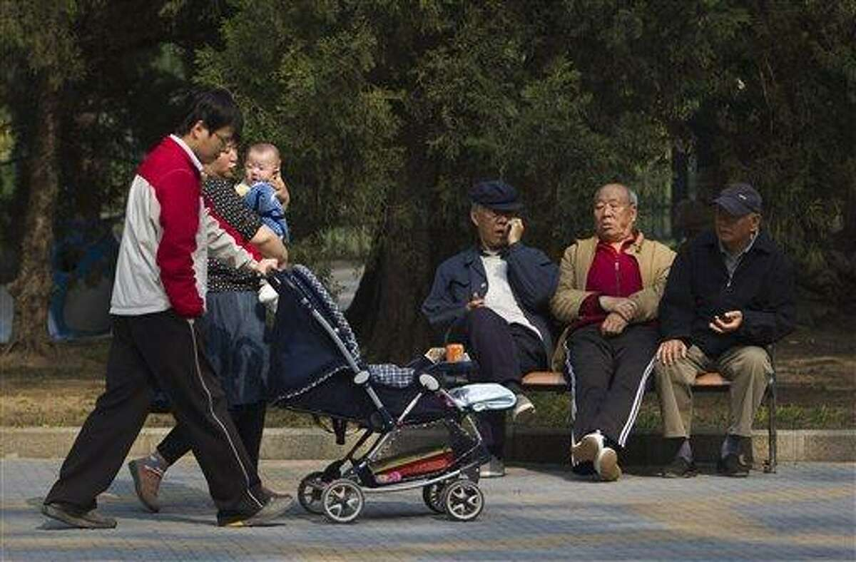 """Elderly men rest on a bench as a family with their new born baby walk past at a park in Beijing, China in 2011. China amended Friday its law on the elderly to require that adult children visit their aged parents """"often"""" - or risk being sued by them. Associated Press file photo"""