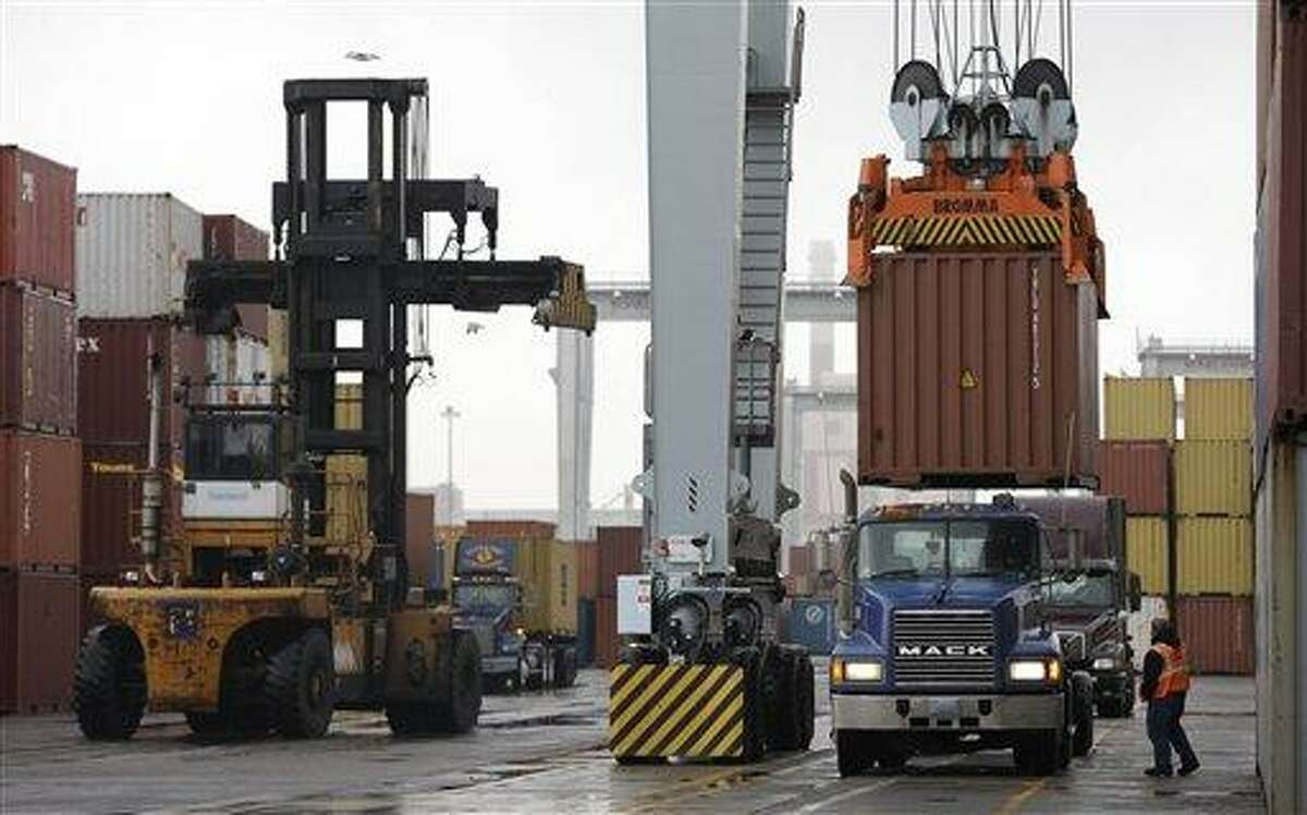A truck driver watches as a freight container, right, is lowered onto a tractor trailer by a container crane at the Port of Boston Dec. 18 in Boston. The crane and a reach stacker, left, are operated by longshoremen at the port. A strike was avoided by the longshoremen's union with a 30-day contract extension Friday as negotiations continue. Associated Press file photo