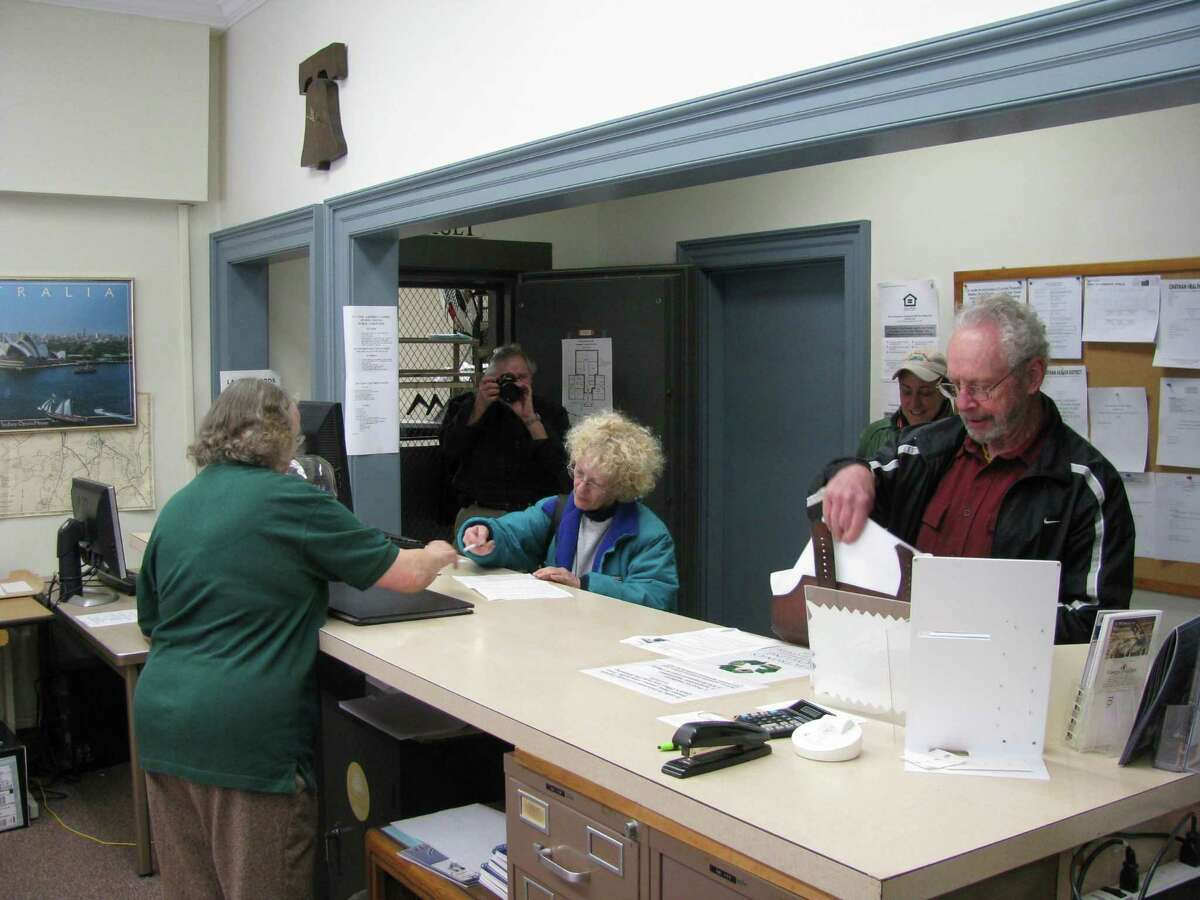 Ed Schwing I Special to the Press Sharon Botelle and Gerry Matthews hand their petitions in to Haddam Town Clerk Ann Huffstetler.