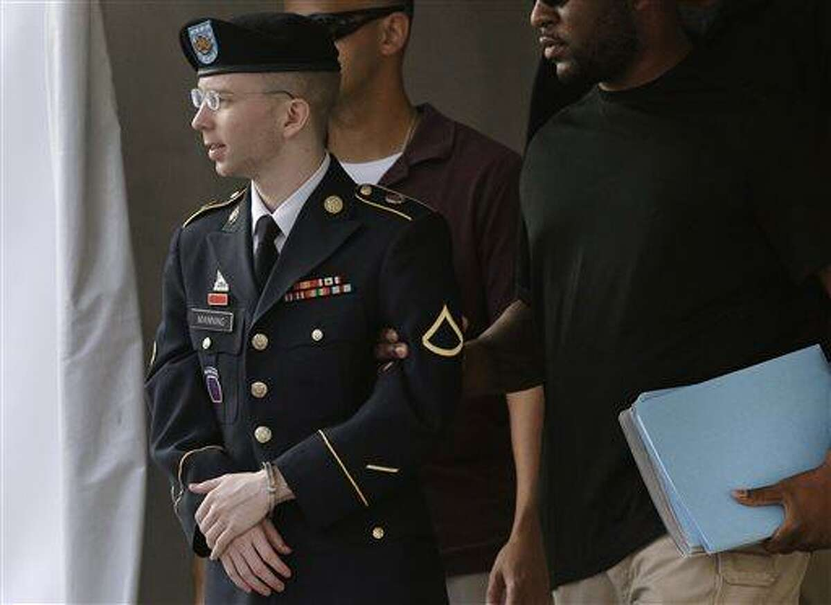 Army Pfc. Bradley Manning, left, is escorted to a security vehicle outside a courthouse in Fort Meade, Md., Thursday, July 18, 2013, after a court martial hearing. Col. Denise Lind, the military judge overseeing Manning's trial, refused a defense request to dismiss a charge that Manning aided the enemy by giving reams of classified information to the anti-secrecy website WikiLeaks. It is the most serious charge he faces, punishable by up to life in prison without parole if found guilty. (AP Photo/Patrick Semansky)