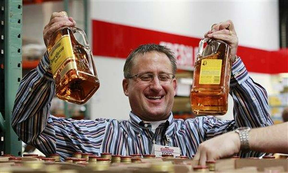In this June 1, 2012 file photo, store manager Todd Young smiles as he restocks tequila at a Costco warehouse store, in Seattle. Private retailers begin selling spirits for the first time under a voter-approved initiative kicking the state out of the liquor business. Liquor privatization was was voted among the state's top news stories of 2012 by Associated Press member editors. (AP Photo/Elaine Thompson, File)