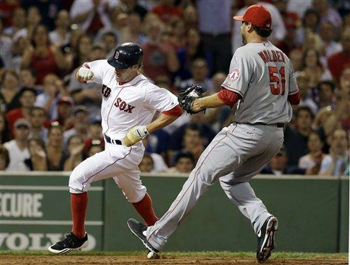 Boston Red Sox's Scott Podsednik scores on a wild pitch by Los Angeles Angels relief pitcher Jordan Walden (51), who runs in to cover home during the seventh inning of a baseball game in Boston on Tuesday, Aug. 21, 2012. (AP Photo/Elise Amendola)