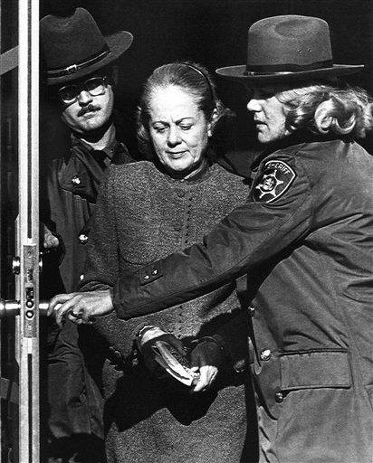 """In this March 20, 1981 file photo, Jean Harris, handcuffed and carrying a book, leaves the Westchester County Jail enroute to the Westchester County Courthouse in Valhalla, N.Y. Harris, the patrician girls' school headmistress who spent 12 years in prison for the 1980 killing of her longtime lover, """"Scarsdale Diet"""" doctor Herman Tarnower, in a case that rallied feminists and inspired television movies, died Sunday, Dec. 23, 2012, in New Haven, Conn. She was 89. AP Photo/Ron Frehm, File"""