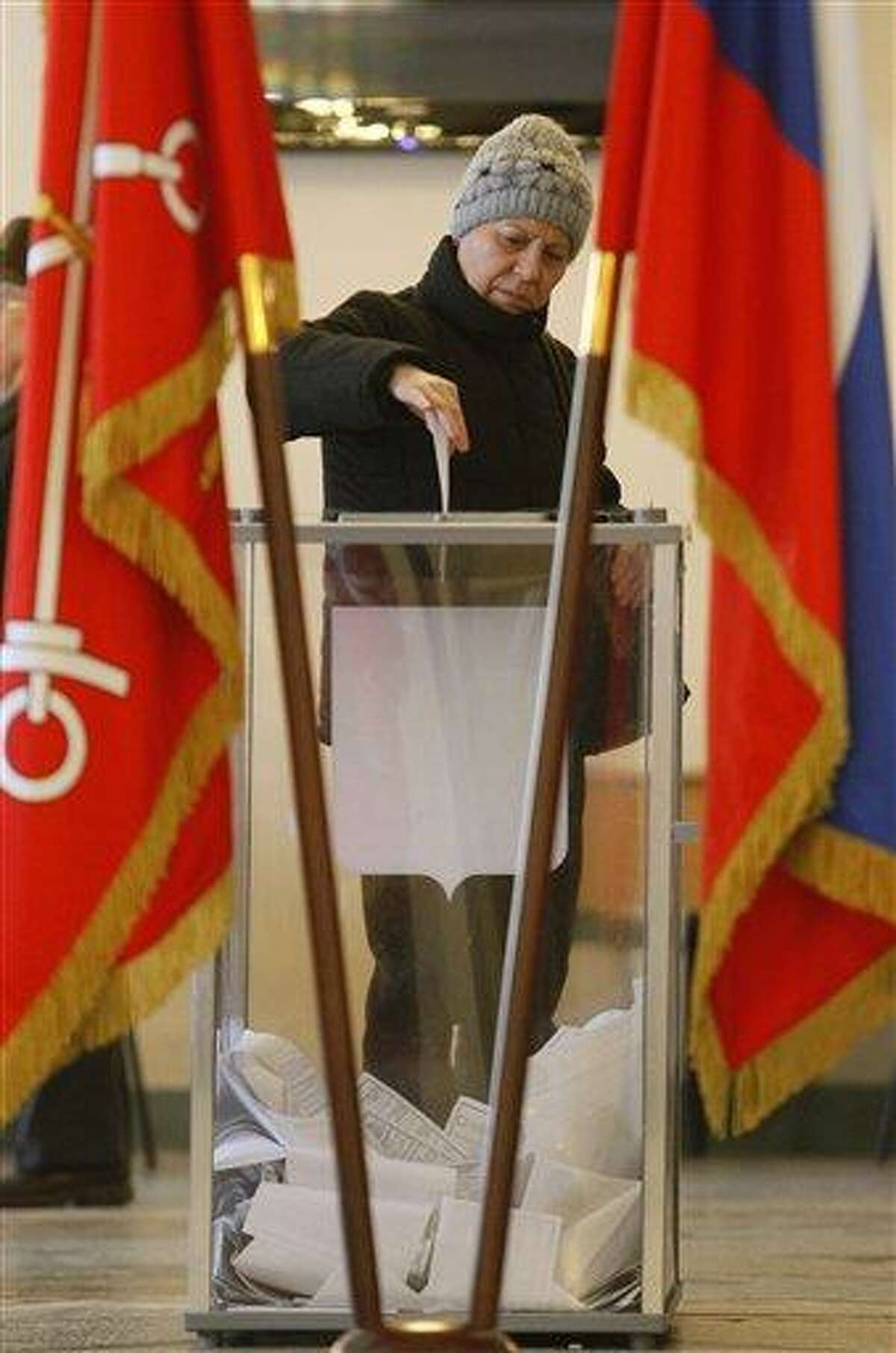 A woman casts her ballot at a polling station during presidential elections in St. Petersburg, Russia, Sunday. Polling stations have opened across Russia's vast expanse for the presidential election widely expected to return Vladimir Putin to the Kremlin. Associated Press