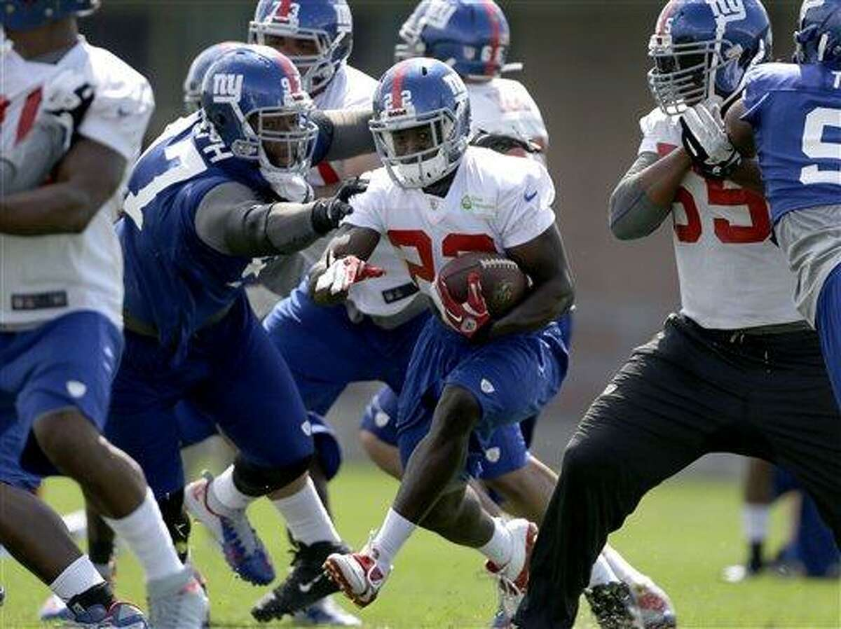 New York Giants running back David Wilson (22), center, runs the ball during NFL football camp in East Rutherford, N.J., Monday, July 29, 2013. (AP Photo/Seth Wenig)