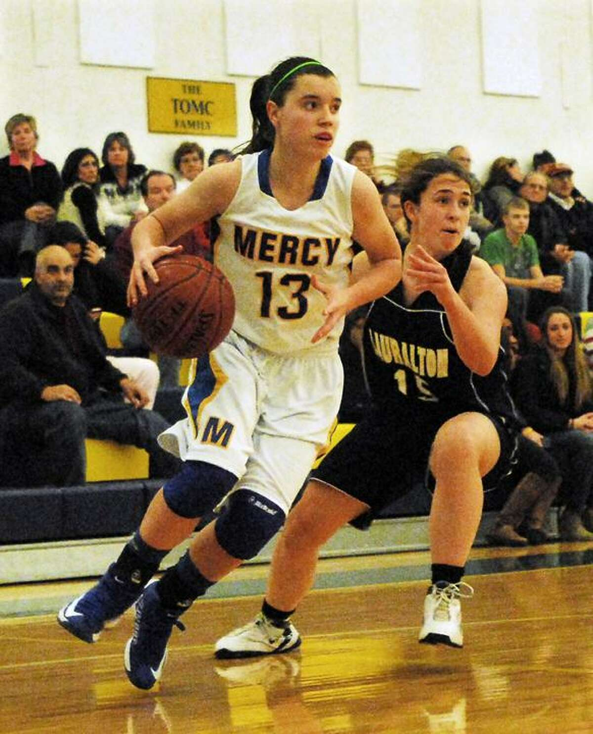 Catherine Avalone/The Middletown Press Mercy senior captain Maria Weselyj drives as Lauralton Hall junior Maureen Connolly defends during the Mercy Classic championship game Friday night. The Mercy Tiges defeated the Lauralton Hall Crusaders 66-47.