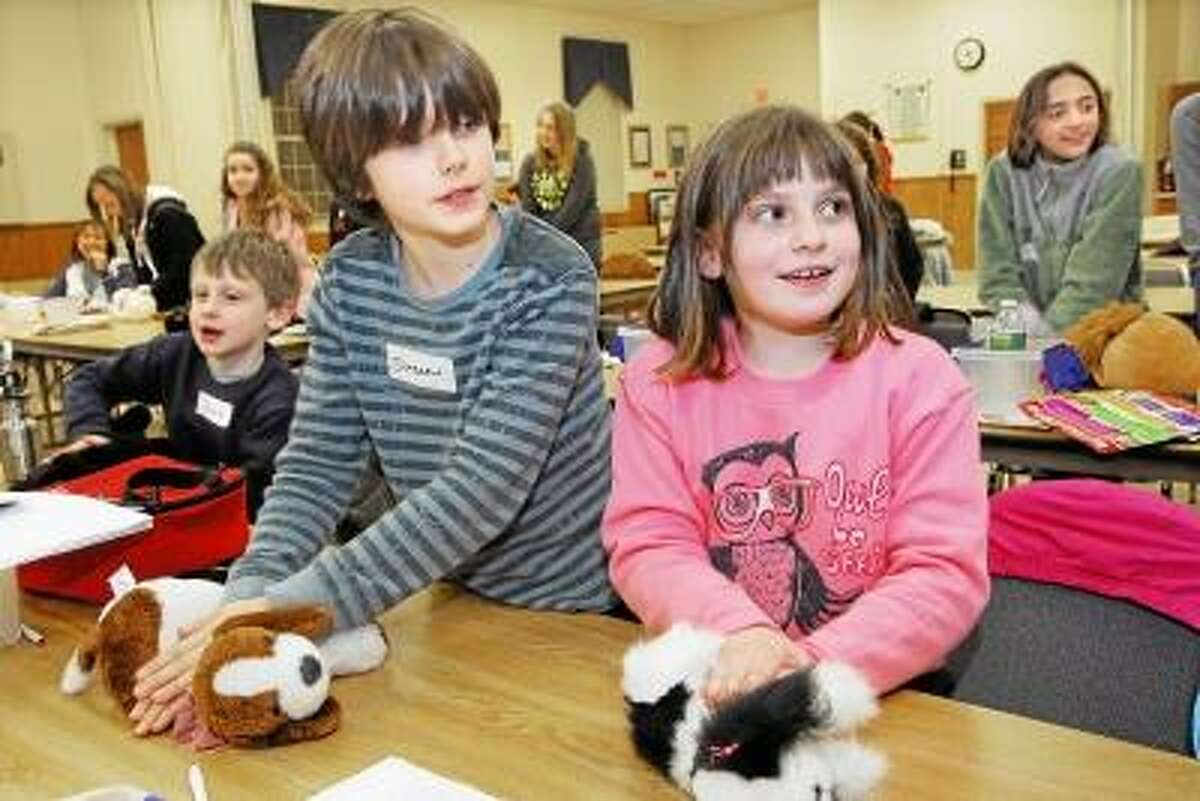Catherine Avalone/The Middletown Press Jonah Kiethan, Duncan Beauchamp, 8, and Madeline Kiethan, 8, both of Higganum, left to right, use stuffed animals to learn CPR from veternarian technician Katie Hanks, employed at Piper-Olson Veterinary Hospital in Middletown. Hanks, a certified instructor with the Red Cross Pet First Aid & CPR taught the three hour course at the Middlesex Cooperative Extension Center in Haddam. The event was organized by the Bad to the Bone 4-H Dog Club in East Hampton which is sponsored by Shagbark Lumber and Paws 'n Heel Dog Training.