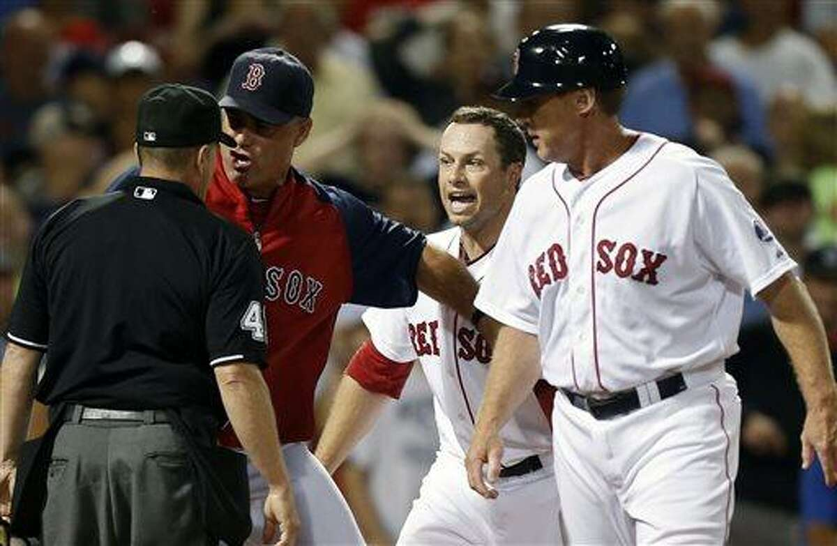 Boston Red Sox manager John Farrell, center left, and Daniel Nava, center right, argue a call with home plate umpire Jerry Meals, left, as third base coach Brian Butterfield, right, looks on in the eighth inning of a baseball game against the Tampa Bay Rays in Boston, Monday, July 29, 2013. The Rays won 2-1. (AP Photo/Michael Dwyer)