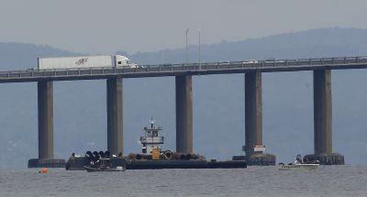 Rescue workers on boats search near a construction barge on the Hudson River in Piermont, N.Y. on Saturday, July 27, 2013, south of the Tappan Zee Bridge for two people who are believed to have fallen into the water during a boat crash.