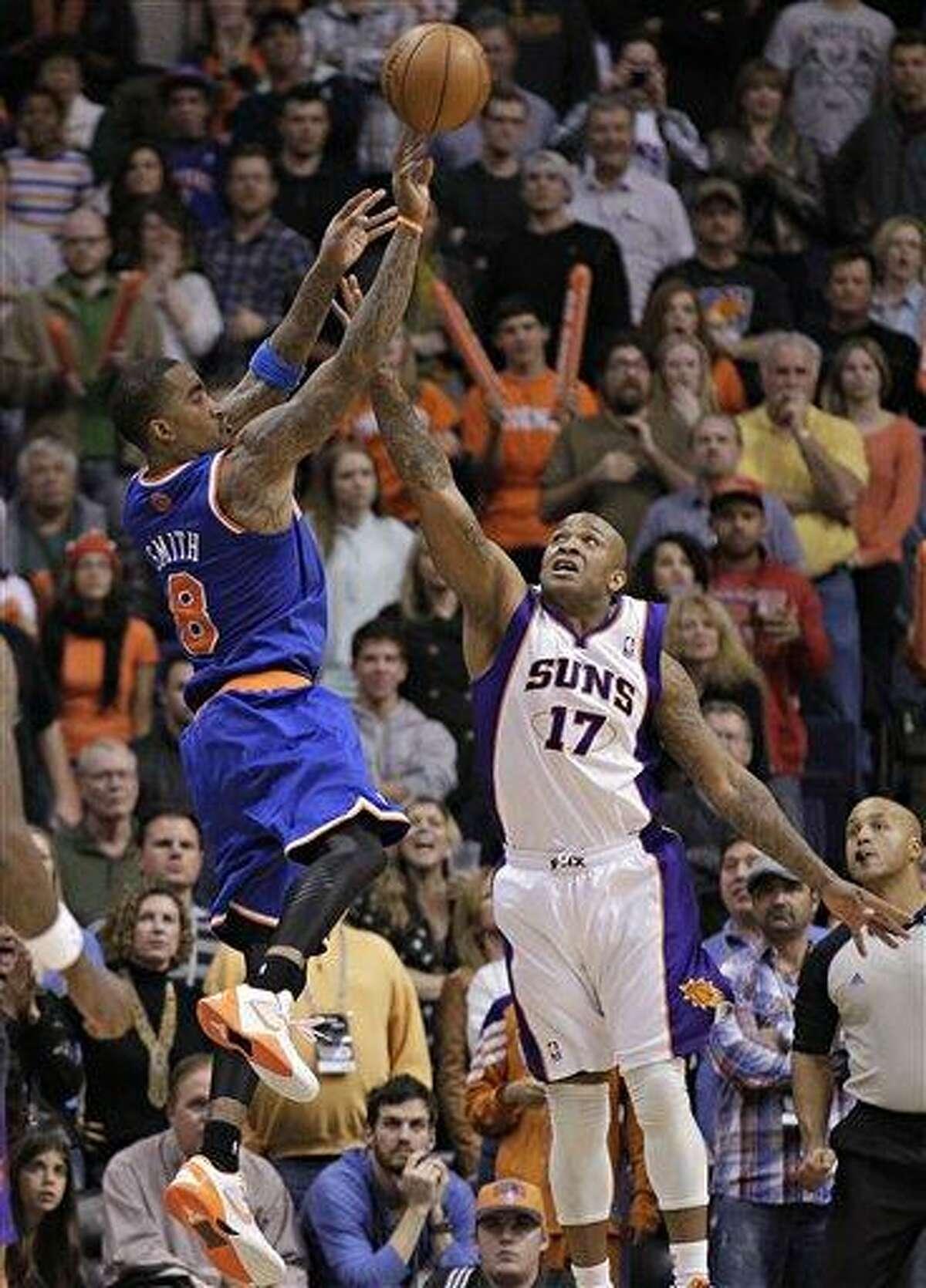 New York Knicks' J.R. Smith (9) takes the game-winning shot over Phoenix Suns' P.J. Tucker (17) during the second half of an NBA basketball game, Wednesday, Dec. 26, 2012, in Phoenix. The Knicks won 99-97. (AP Photo/Matt York)