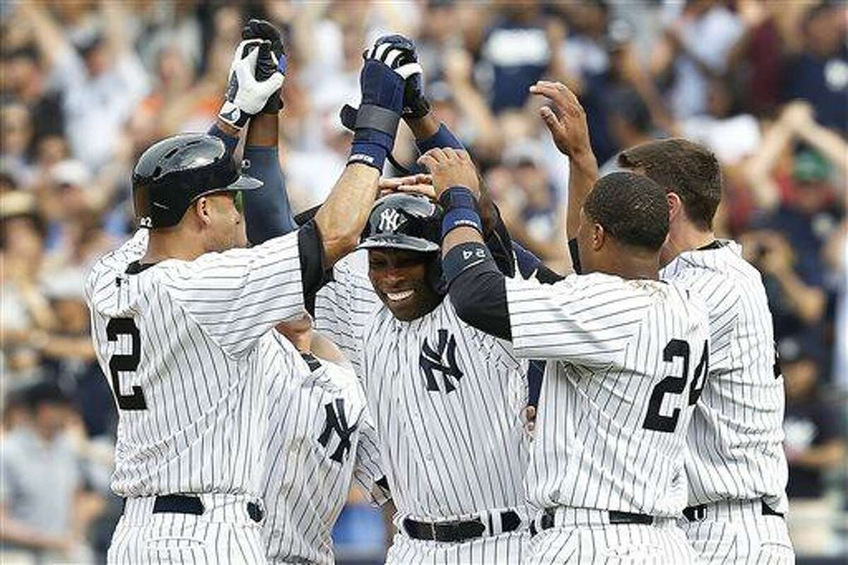 Teammates celebrate with New York Yankees' Alfonso Soriano, center, after he drove home the game-winning run in a baseball game against the Tampa Bay Rays, Sunday, July 28, 2013, in New York. The Yankees defeated the Rays 6-5. (AP Photo/John Minchillo)