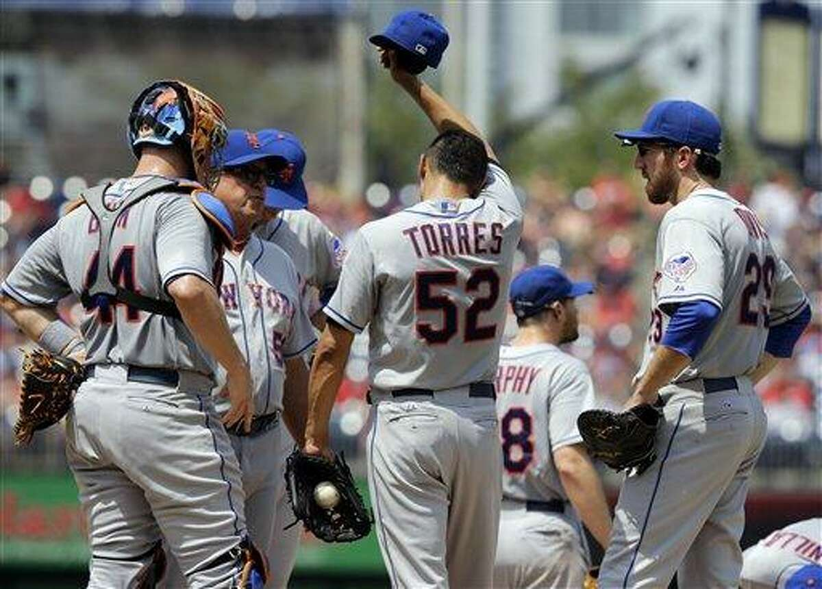 New York Mets pitching coach Dan Warthen (59), second from left, talks with New York Mets starting pitcher Carlos Torres (52) during a baseball game against the Washington Nationals at Nationals Park Sunday, July 28, 2013, in Washington. (AP Photo/Alex Brandon)