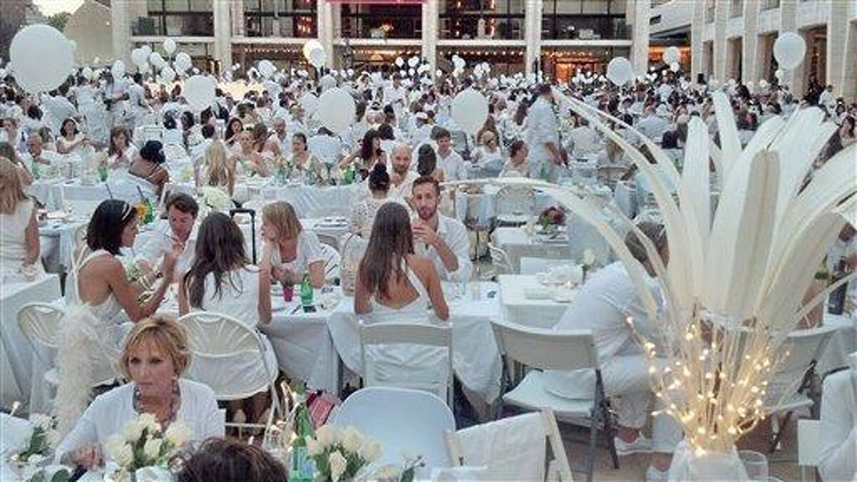 An estimated 3,000 people, all dressed in white, attend a flash mob feast on Monday at the Lincoln Center for the Performing Arts in New York. The venue was a secret until just before the dinner started at 7 p.m. when registered guests got emails telling them where to go. (AP Photo/Verena Dobnik)