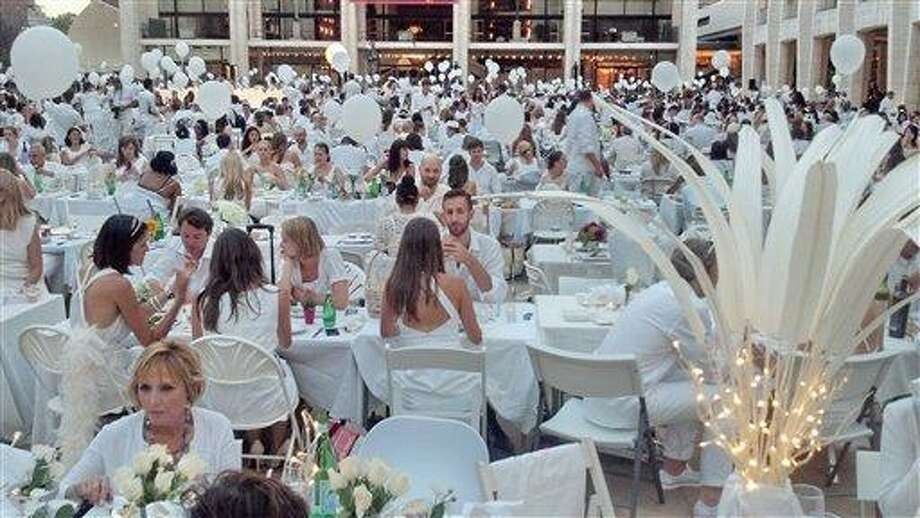 An estimated 3,000 people, all dressed in white, attend a flash mob feast on Monday at the Lincoln Center for the Performing Arts in New York. The venue was a secret until just before the dinner started at 7 p.m. when registered guests got emails telling them where to go.  (AP Photo/Verena Dobnik) Photo: AP / AP