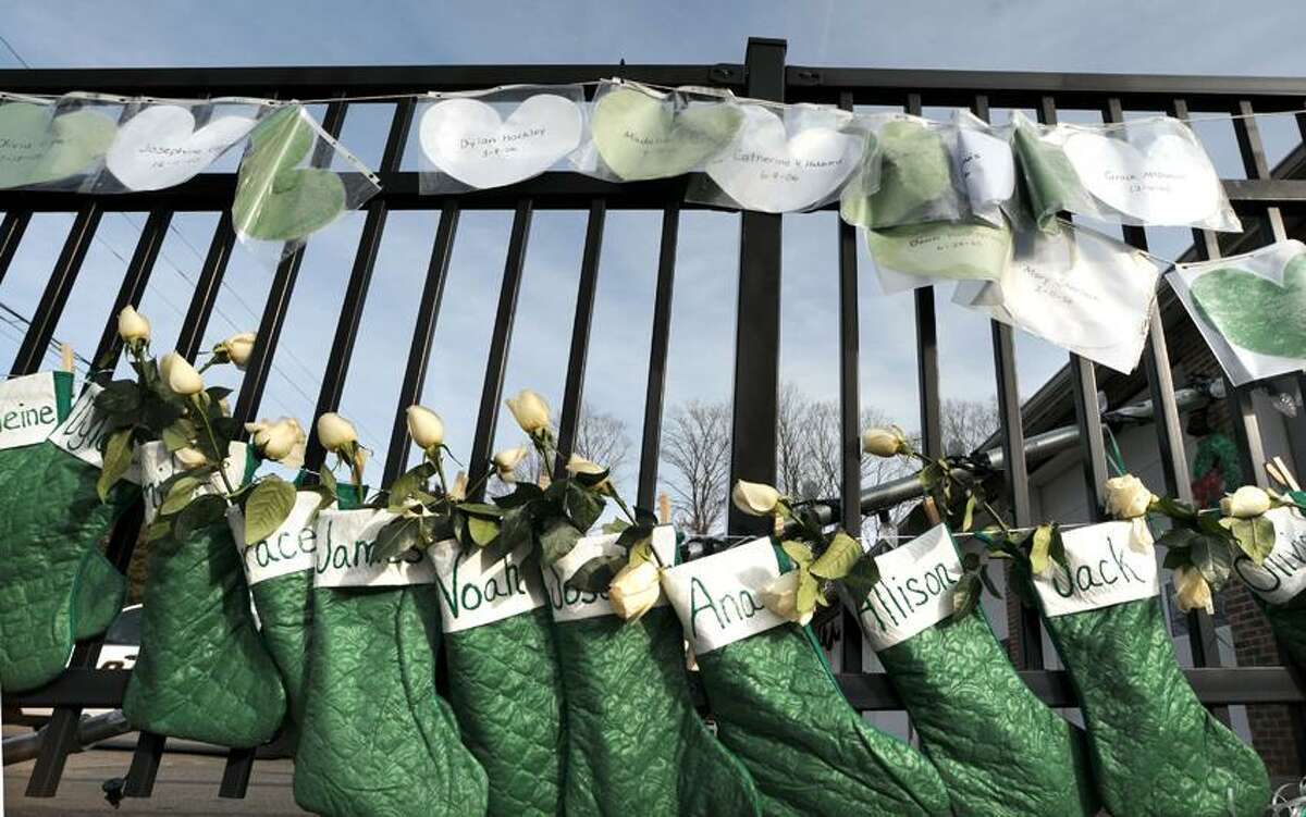 Christmas stockings, hearts and roses in Newtown's school colors decorate the fence alongside the Sandy Hook Volunteer Fire and Rescue Dept. on Riverside Rd. Mara Lavitt/New Haven Register12/24/12