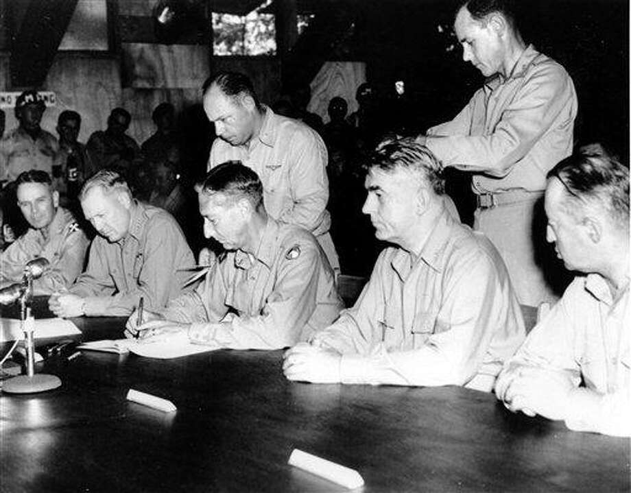 FILE - In this July 30, 1953 black-and-white file photo, Commander-in-chief, United Nations Command, and U.S. Army Gen. Mark Clark signs the Military Armistice agreement at a base camp at Munsan-ni, Korea. Sixty years after it finished fighting in Korea, the U.S. is still struggling with two legacies that are reminders of the costs -- political, military and human -- that war can impose on the generations that follow. The first is the leading role that America still is committed to playing in defending South Korea should the 1950-53 Korean War re-ignite. (AP Photo, File) Photo: AP / AP