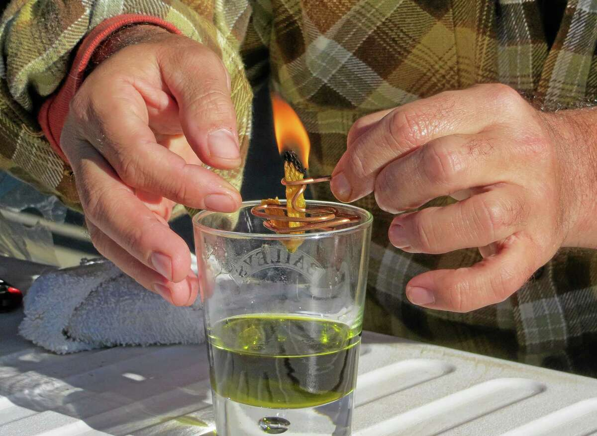 In this Oct. 5, 2013 photo, Derek Cross, a chef who specializes in cooking with hemp, demonstrates the burning properties of hemp oil, which he touts as a digestible bio fuel, during the first known harvest of industrial hemp in the U.S. since the 1950s, at a farm in Springfield, Colo. America is one of hemp's fastest-growing markets, with imports largely coming from China and Canada. Most of that is hemp seed and hemp oil, which finds its way into granola bars, soaps, lotions and even cooking oil. (AP Photo/Kristen Wyatt)