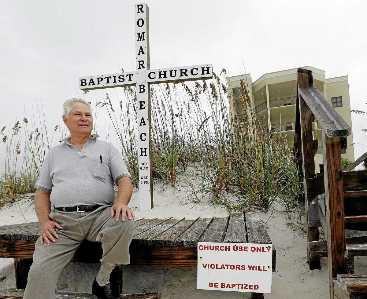 Romar Beach Baptist Church Pastor Paul Smith sits on a platform that holds a cross at the end of the boardwalk leading to the beach in Orange Beach, Ala., Sunday, Oct. 6, 2013. The hurricane proof church built welcomes all and provides shelter for it's members and others in need when storms threaten the coast. (AP Photo/Dave Martin)