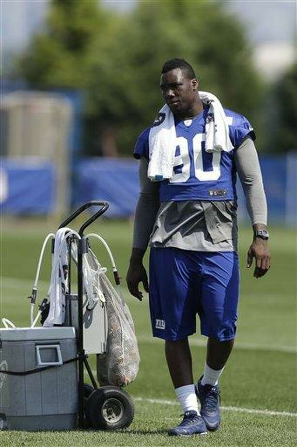 New York Giants defensive end Jason Pierre-Paul looks on during NFL football camp in East Rutherford, N.J., Saturday, July 27, 2013. (AP Photo/Julio Cortez) Photo: AP / AP