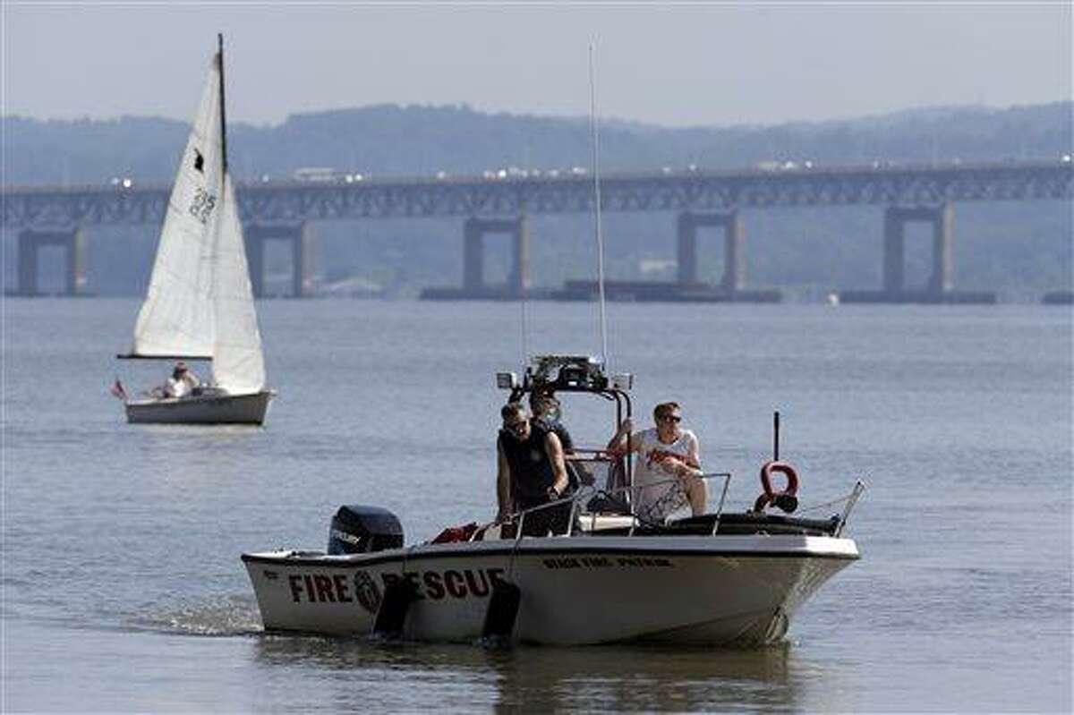 Rescue workers on a boat search the Hudson River south of the Tappan Zee Bridge for two people who went missing following a boat crash in Piermont, N.Y. on Saturday, July 27, 2013. Two people are missing and four others are injured after their boat struck a barge under the bridge, according to the Coast Guard. (AP Photo/Julio Cortez)