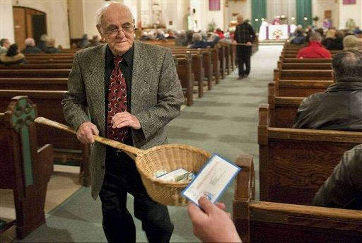 In this 2009 file photo, John Alves, of Dartmouth, Mass., uses a basket while taking collection during Mass at St. John the Baptist Roman Catholic Church in New Bedford, Mass. A study on the generosity of Americans by the Chronicle of Philanthropy released Monday found that states with populations that are less religious are also the stingiest about giving money to charity. Associated Press