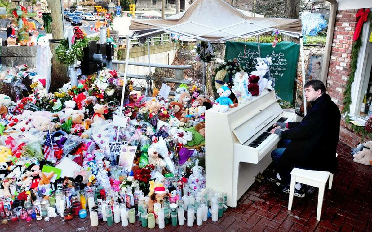 Julian Revie of Ottawa, Canada, plays Christmas music on the piano for visitors to makeshift memorials for the victims of the Sandy Hook Elementary School shootings in downtown Sandy Hook on Christmas 12/25/2012.Photo by Arnold Gold/New Haven Register