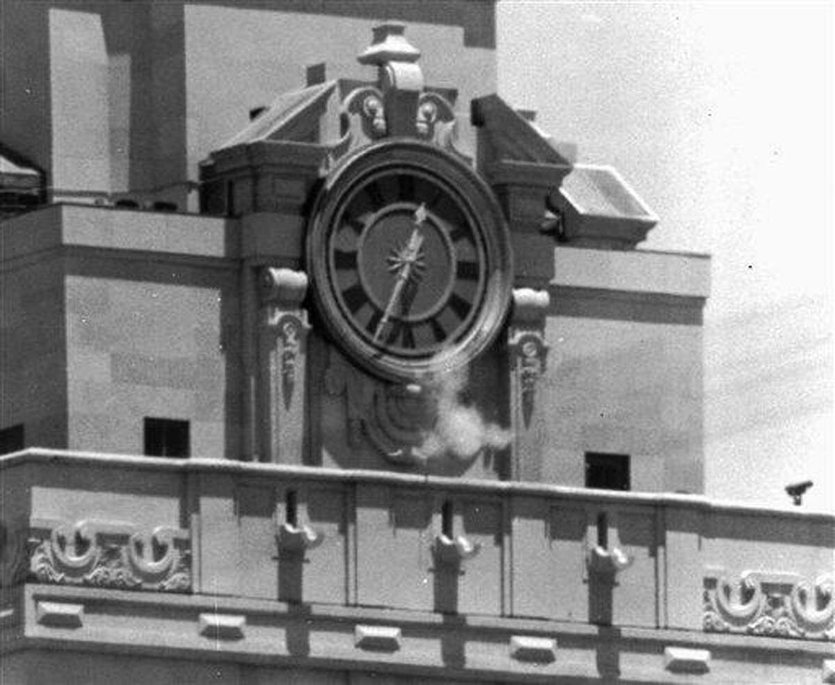 FILE - In this Aug. 1, 1966 file photo, smoke rises from a sniper's gun as he fires from the tower of the University of Texas administration building in Austin, Texas at people below. Grant Duwe, a criminologist with the Minnesota Department of Corrections, says,