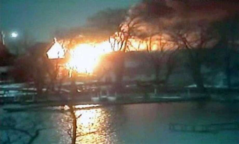 This image taken from video provided by WHAM13-TV, shows a wide view of homes on fire in an area where a gunman ambushed four volunteer firefighters responding to an intense pre-dawn house fire early Monday, Dec. 24, 2012, in Webster, N.Y., killing two before ending up dead himself, authorities said. Police used an armored vehicle to evacuate more than 30 nearby residents. (AP Photo/WHAM13-TV via AP video) Photo: AP / WHAM13-TV via AP video