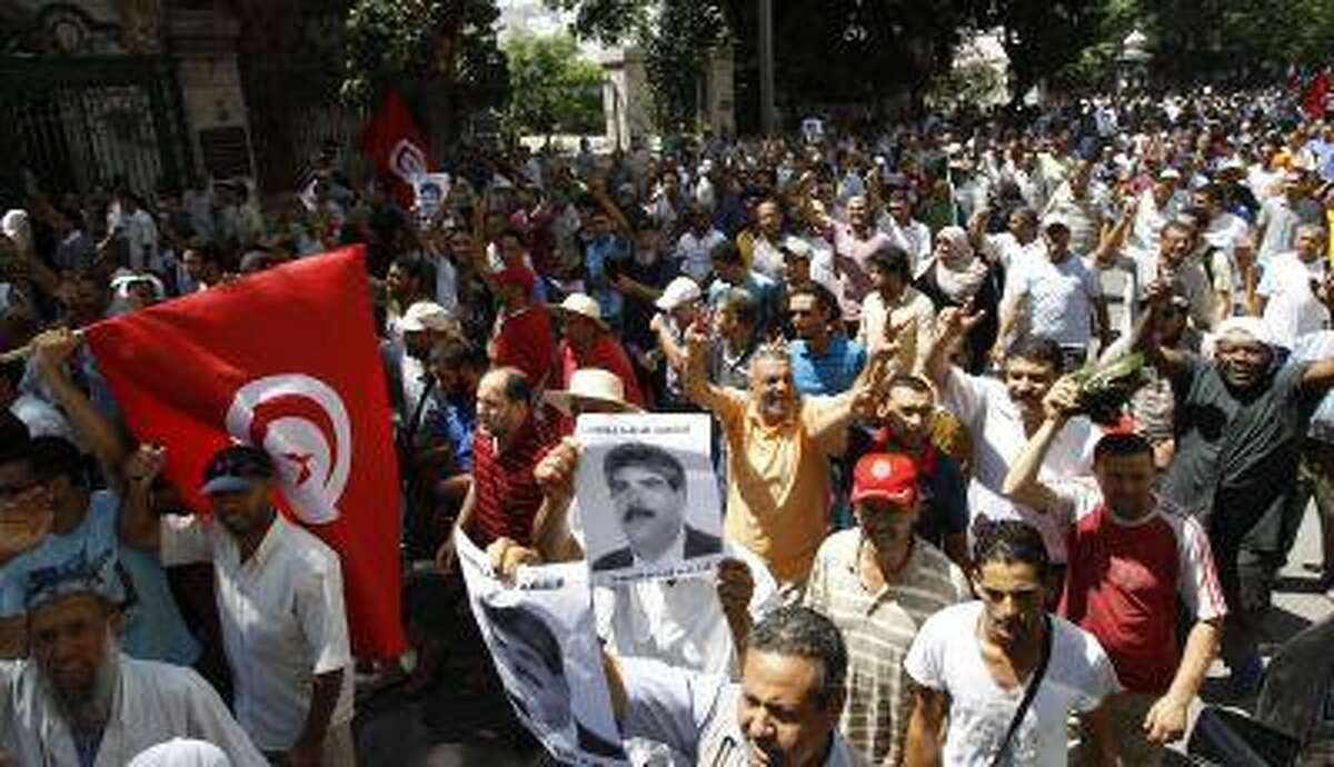 Supporters of the Islamist Ennahda movement wave flags as they chant slogans and hold pictures of assassinated opposition politician Mohamed Brahmi during a demonstration in Tunis July 26, 2013.