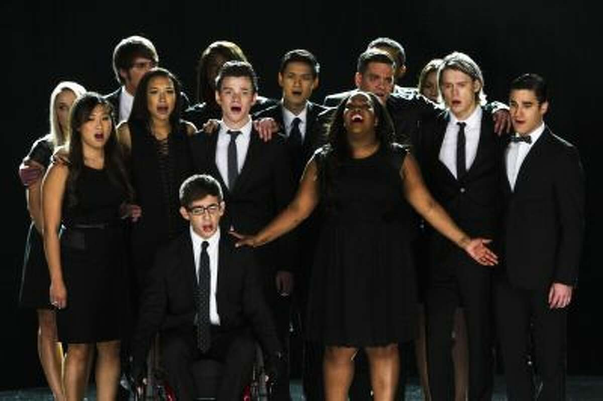 """This photo released by Fox shows the McKinley family of the past and present joining together to remember and celebrate the life of Finn Hudson in """"The Quarterback"""" episode of """"Glee."""" The high school musical drama said goodbye to Finn, its beloved singer-quarterback, while paying tribute to Cory Monteith, the late actor who had portrayed him, in a much-anticipated episode that aired Thursday, Oct. 10, 2013."""