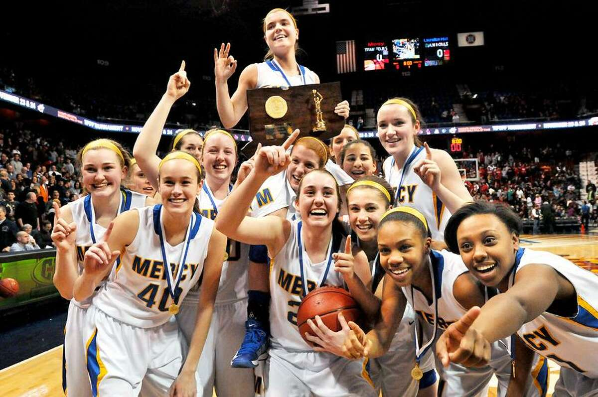 Catherine Avalone/The Middletown Press Mercy senior captain Maria Weselyj is lifted by her onto the shoulders of Liz Falcigno by her teammates after hitting a 3 point buzzer shot to defeat Lauralton Hall-Milford 54-53 in the Class LL State Championship game at Mohegan Sun Saturday evening.