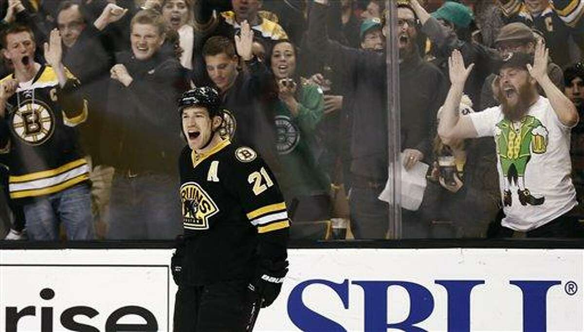 Fans celebrate with Boston Bruins' Andrew Ference after he scored against the Washington Capitals during the second period of an NHL hockey game in Boston, Saturday, March 16, 2013. (AP Photo/Winslow Townson)