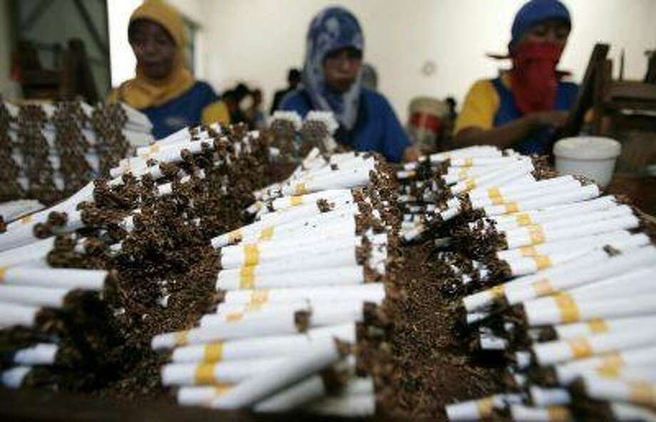 Workers roll cigarettes in a factory in Sidoarjo, East Java province February 2, 2009. REUTERS/Sigit Pamungkas / X02312