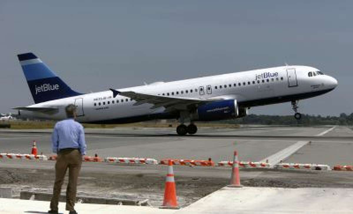 In this Wednesday, June 2, 2010 photo, a man watches a JetBlue airplane take off from John F. Kennedy International Airport in New York.